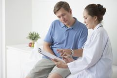 Discussing medical tests results. Female doctor showing document with medical tests results to male pateint royalty free stock image