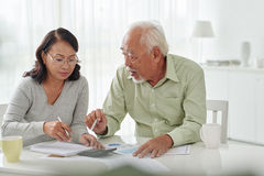 Discussing papers. Senior Asian business couple discussing financial documents Royalty Free Stock Photography