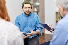 Discussing Phobia at Group Therapy Session. Depressed bearded men wearing denim shirt discussing his phobia with highly professional psychologist and other royalty free stock image