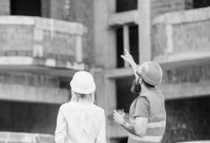 Discussing plan. Woman engineer and builder communicate at construction site. Relationships between construction clients royalty free stock photo
