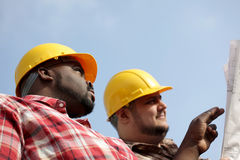 Discussing plans. Construction workers at building site Stock Photography