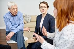 Discussing Problems at Group Therapy Session. Red-haired obese women discussing faced problem with other patients and highly professional psychologist while royalty free stock photography