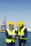 Discussing a procedure. Two dockers discussing procedures and plans at the waters edge Royalty Free Stock Photo