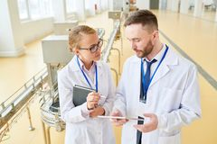 Discussing Production Quantity with Colleague. Handsome bearded technologist wearing white coat showing statistic data concerning production quantity to female royalty free stock photos