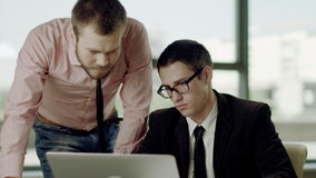 Discussing project. Two men discussing project looking at laptop and talking to each other stock footage