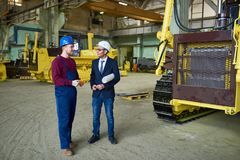 Discussing promising project with superior. Smiling young technician wearing overall and hardhat sharing ideas with his superior while discussing promising Stock Photography