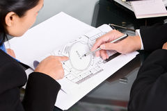 Discussing property planning. Two business people discuss about the property plan by showing the map Stock Photos