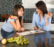 Discussing recipes. Two friends discussing recipes over a cookbook Stock Photography