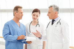 Discussing the report. Hospital doctors discussing the patient's Stock Photo