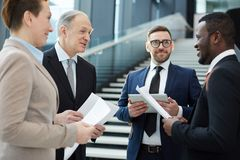 Discussing reports. Group of intercultural business partners or delegates in suits discussing their ideas for reports before conference Royalty Free Stock Image