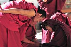 Discussing scriptures monks in Tibet. Tibetan monks at Sera monastery debating in the courtyard Royalty Free Stock Photos
