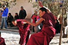 Discussing scriptures monks in Tibet. Tibetan monks at Sera monastery debating in the courtyard Royalty Free Stock Image