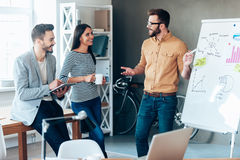 Discussing some new project together. Confident young men standing near whiteboard and pointing it with smile while his colleagues standing near him Royalty Free Stock Image