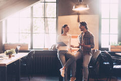 Discussing some working issues. Cheerful young men and women discussing something and smiling while both leaning at the wooden desk in creative office royalty free stock image