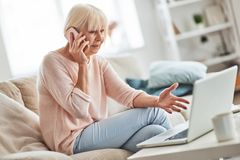Discussing something important. Beautiful senior woman talking on her smart phone and gesturing while relaxing on the couch at home stock photography
