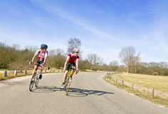 Discussing tactics. Two cyclists discussing the tactics of their escape, now leading the race Royalty Free Stock Images