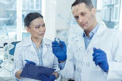 Concentrated scientists working on their research. Discussing work. Good-looking concentrated smart experienced scientists wearing uniforms and writing formulas Royalty Free Stock Images