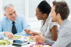 Discussing of Work at Lunch. Business Colleagues Eating Meal Together While Discussing of Work Stock Photo