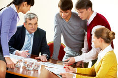 Discussion. Photo of boss surrounded by colleagues during discussion Royalty Free Stock Photography