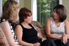 Discussion. Three Women At A Home Party Having A Discussion stock photo