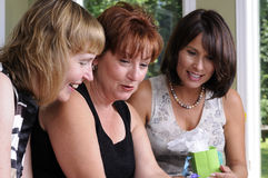 Discussion. Three Women At A Home Party Having A Discussion Stock Photos