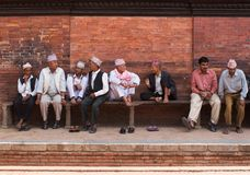 Discussion on a bench. PATAN, NEPAL - MAY 09: Group of nepalese men on a wooden bench  are discussing news of  today in Patan, Nepal on May 09, 2008. Travel in Stock Photo