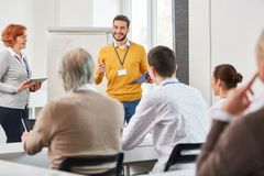 Discussion in business training seminar. Lecturer with group of people in discussion at business training seminar royalty free stock image