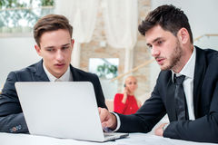 Discussion of business. Two successful and confident businessman. Sitting at the table in a business office in full costume in the office and working at a Stock Images
