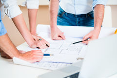 Discussion of construction plans in architects office. Civil engineers in discussion of construction plans for building in architect office Royalty Free Stock Photography