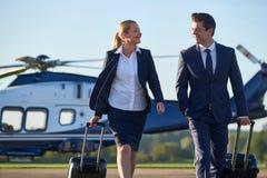 Discussion d'And Businessman In de femme d'affaires comme ils marchent à partir de l'hélicoptère photographie stock