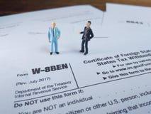Discussion de deux hommes d'affaires au sujet de la feuille d'impôt des Etats-Unis, w-8ben, certificat de statut étranger de prop photographie stock