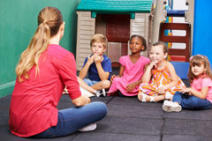 Discussion group of children in kindergarten. Talking to nursery teacher royalty free stock photo