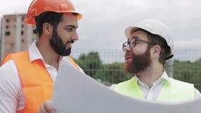 Discussion masculine de sourire d'ingénieur de construction avec l'architecte au chantier de construction ou au chantier du gratt banque de vidéos