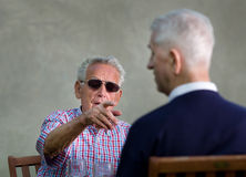 Discussion. Old men with black sunglasses pointing forefinger in another old man Royalty Free Stock Image
