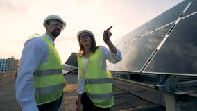 Discussion process of two solar experts held near a solar construction. Solar energy concept. Discussion process of two solar experts held near a solar stock footage