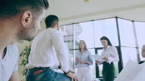 Discussion in the spacious office Camera sliding around people is topping on the man with papers in hands Thinking about