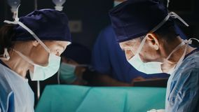 Discussion of two surgeons during serious operation. In dark operating room stock footage