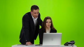 Discussion of working moments of two colleagues in the office. Woman sitting at a table on which is open laptop and landline phone, open notebook, man standing stock footage