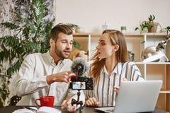 Discussione calda Maschio emozionale e blogger femminili che discutono argomento interessante mentre online scorrendo fotografia stock