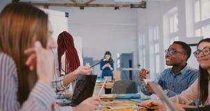 Discussione creativa multietnica positiva felice del gruppo alla riunione d'avanguardia moderna dell'ufficio, capo nero della don stock footage