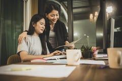 Discussione indipendente della più giovane donna asiatica due al lavoro sull'ufficio co fotografia stock