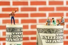Discussione miniatura delle figurine sull'orlo di un banknot di 100 dollari Fotografia Stock