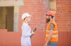 Discuta el plan del progreso Concepto del sector de la construcci?n Ingeniero de la mujer y constructor brutal barbudo discutir l imagenes de archivo