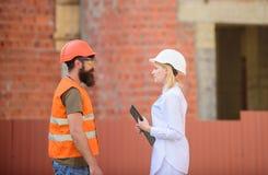 Discuta o plano do progresso Conceito da indústria da construção civil Coordenador da mulher e construtor brutal farpado para dis imagem de stock