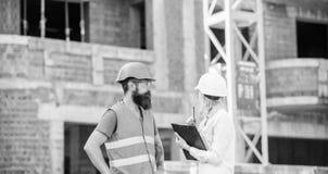 Discuta o projeto do progresso Conceito do inspetor da seguran?a Inspetor e construtor brutal farpado para discutir o progresso d imagens de stock royalty free