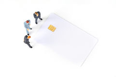 Discutendo gli uomini d'affari miniatura con la chip card Fotografie Stock