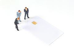 Discutendo gli uomini d'affari miniatura con la chip card Fotografia Stock