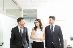 Discutindo matérias de negócio ao andar no escritório foto de stock royalty free