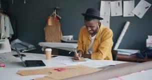 Diseñador afroamericano del hombre que escribe en el funcionamiento del cuaderno en estudio solamente metrajes