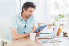 Diseñador casual que usa la tableta de gráficos y el ordenador portátil imágenes de archivo libres de regalías